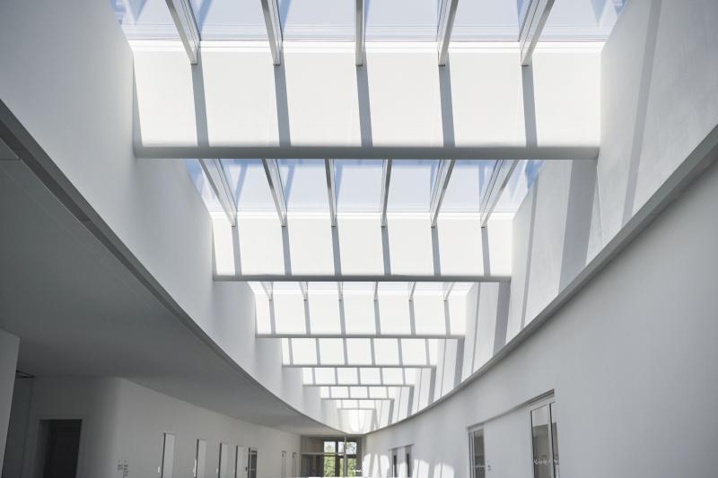 Das ellipsenförmige Atrium-Sattel-Lichtband nimmt die Form des Laborgebäudes auf und wird zum architektonischen Blickfang im gesamten Gebäude. Fotos: Velux / Jesper Blaesild